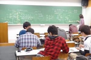 授業の類似プリントの解説を聞いて友達どうしで相談しながら復習する学生